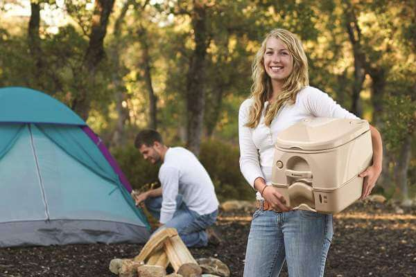 Woman holding a portable toilet on a campsite