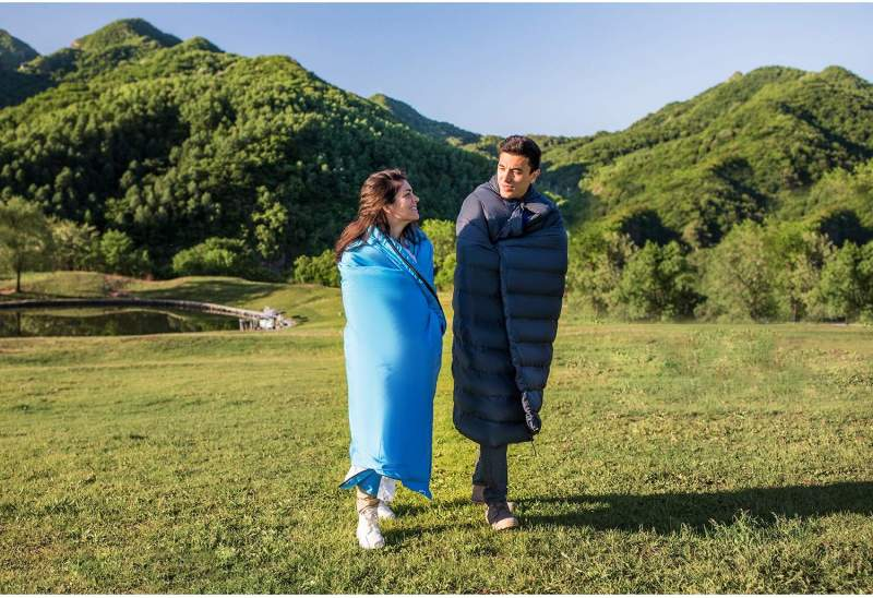 a couple walking outdoors wrapper in sleeping bags