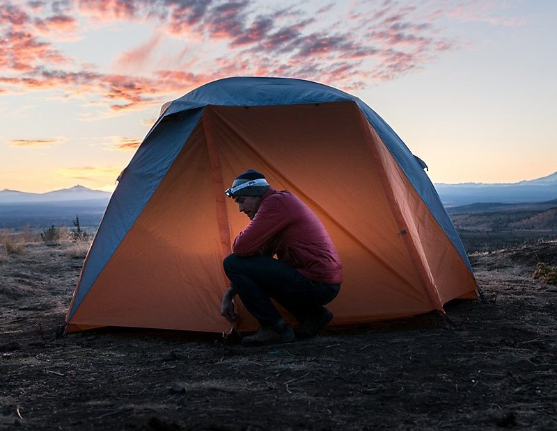 a man knelt beside a marmot limestone tent outdoors