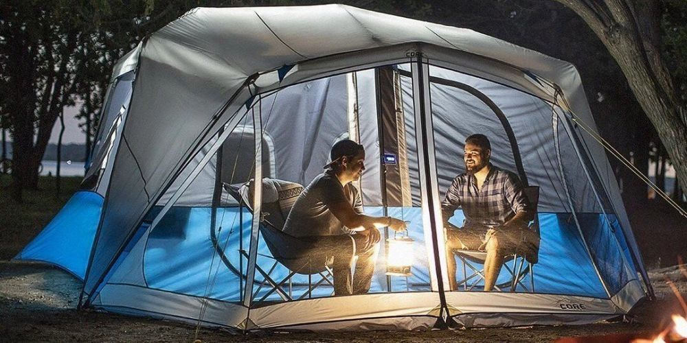 2 campers inside a tent with a camping light