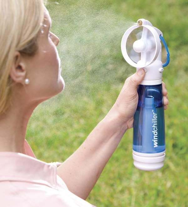 a woman using a handheld misting fan