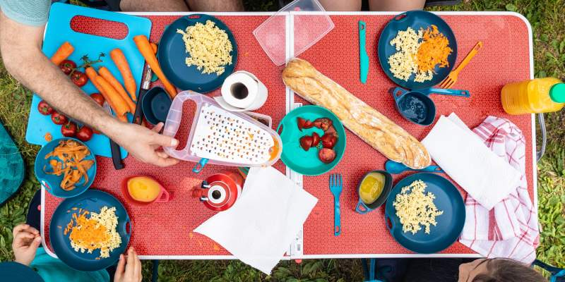 a camping table covered in cooking utensils and food
